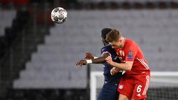 Gelandang PSG, Idrissa Gueye (kiri) berebut bola udara dengan gelandang Bayern Munchen, Joshua Kimmich pada pertandingan leg kedua perempat final Liga Champions di Parc des Princes stadium, Paris, Selasa (14/4/2021). PSG sukses melaju ke semifinal berkat kemenangan 3-2 di kandang Munchen. (AFP/Franc