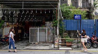 Turis lokal mengambil foto di sepanjang kawasan tua di Penang (1/8/2020). Malaysia tengah memperingatkan gelombang kedua virus corona COVID-19. (AFP Photo/Goh Chai Hin)