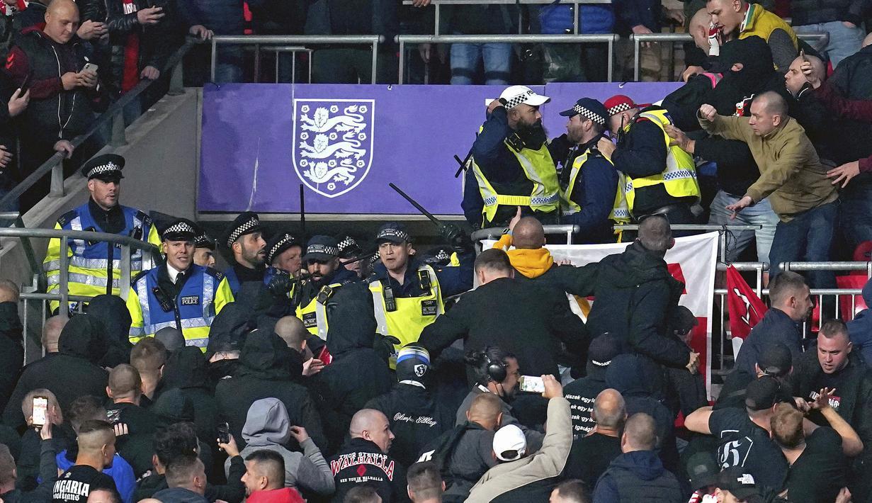 Suporter Hungaria bentrok dengan polisi saat dimulainya laga Kualifikasi Piala Dunia 2022 melawan Inggris di Stadion Wembley, Rabu (13/10/2021) dini hari WIB. Bentrokan terjadi saat polisi berusaha menangkap penonton yang melakukan pelecehan rasial terhadap petugas stadion. (Nick Potts/PA via AP)