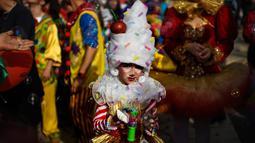 Seorang anak yang mengenakan pakaian badut ikut serta dalam parade badut tahunan di Sesimbra, Portugal pada Senin (4/3/2019). Tidak hanya orang dewasa anak-anak pun ikut merias diri menjadi badut. (PATRICIA DE MELO MOREIRA / AFP)