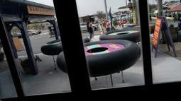 Para tamu bersiap mencoba meja yang bentuknya menyerupai ban pelampung untuk menjaga jarak pelanggan di Fish Tales Bar & Grill di Ocean City, Maryland, Jumat (29/5/2020). Pengunjung akan berdiri di bagian tengah meja bundar itu yang dilengkapi roda untuk memudahkan pergerakan. (Alex Edelman/AFP)