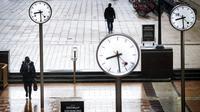 Para penumpang berjalan melalui Canary Wharf yang hampir sepi selama jam sibuk di London, Inggris, 12 Januari 2021. Inggris sedang menerapkan lockdown nasional ketiga untuk mengekang penyebaran virus corona COVID-19. (Victoria Jones/PA via AP)