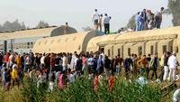 Orang-orang berkumpul di lokasi kecelakaan kereta penumpang dekat Banha, Provinsi Qalyubia, Mesir, Minggu (18/4/2021). Sebanyak 11 orang tewas dan 98 lainnya luka-luka akibat kereta tergelincir dan keluar jalur. (AP Photo/Tarek Wagih)