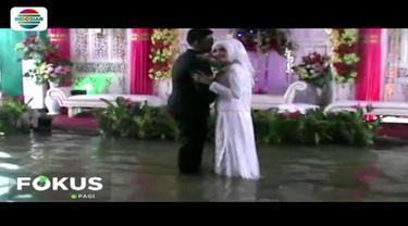 Meski menikah di tengah guyuran hujan dan banjir, pasangan pengantin asal Kebumen ini tampak bahagia. Bahkan mereka melakukan sesi pemotretan di tengah genangan air.