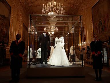 Gaun pernikahan Putri Eugenie dan jas sang suami, Jack Brooksbank ditampilkan selama pratinjau media di Kastil Windsor, London, Kamis (28/2). Gaun tersebut akan dipajang sebagai bagian dari pameran yang berlangsung hingga 22 April 2019. (AP/Matt Dunham)