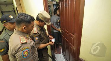 Petugas Satpol PP melakukan razia penghuni kos di kawasan Tebet, Jakarta, Selasa (21/4).  Razia kos ini erat kaitannya dengan kasus pembunuhan wanita berprofesi sebagai PSK online, Deudeuh Alfisahrin. (Liputan6.com/Faizal Fanani)