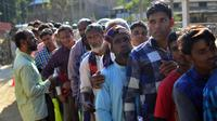 Penduduk Assam di India yang mengantre untuk memeriksakan namanya di National Register of Citizens (NRC), Desa Gumi, Distrik Kamrup. Mereka yang namanya tak tercantum dalam daftar terancam dideportasi (Kulendu Kalita/AP PHOTO via The Guardian)