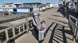 Seorang ibu dan anaknya mendorong koper bawaannya saat tiba di Dermaga Kali Adem, Muara Angke, Jakarta, Minggu (27/12/2020). Sebanyak 3.018 wisatawan berkunjung ke Kepulauan Seribu seperti Pulau Tidung, Pari, dan Pramuka untuk mengisi libur Natal (merdeka.com/Iqbal Nugroho)