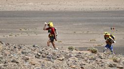 Peserta meminum air saat mengikuti kejuaraan Marathon des Sables ke-32 tahap ketiga di Gurun Sahara, selatan Maroko, Selasa (11/4). Salah satu kompetisi paling berat itu menjadi ajang tahunan sejak 1986 di setiap bulan April. (JEAN-PHILIPPE KSIAZEK/AFP)