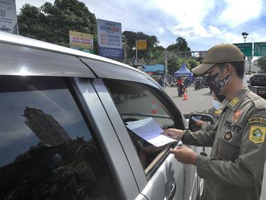 Petugas gabungan Satgas COVID-19 memeriksa surat rapid test antigen pengguna kendaraan di jalur wisata Puncak, Gadog, Bogor, Jawa Barat, Jumat (12/2/2021). Pemeriksaan dan penyekatan sebagai upaya meminimalisir penyebaran COVID-19 saat libur Imlek 2572 dan akhir pekan. (merdeka.com/Arie Basuki)