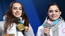 Alina Zagitova (kiri) dan Evgenia Medvedeva dari Rusia tersenyum di atas podium usai pertandingan figure skating putri Olimpiade Musim Dingin Pyeongchang 2018 di Pyeongchang Medals Plaza (23/2). (AFP Photo/Dimitar Dilkoff)