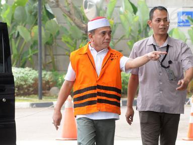 Gubernur Aceh Irwandi Yusuf memakai rompi oranye dikawal petugas saat turun dari mobil tahanan tiba untuk menjalani pemeriksaan lanjutan di gedung KPK, Jakarta, Rabu (25/7). (Merdeka.com/Dwi Narwoko)