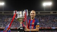 Andres Iniesta memegang trofi Piala Raja Spanyol (Copa del Rey) di stadion Vicente Calderon, Spanyol, Minggu (28/5). Barcelona sukses mempertajam rekornya di kancah Copa del Rey dengan keberhasilan menjadi juara sebanyak 29 kali. (AP Photo)