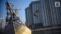 Seorang anak melompat dari atas kapal yang tengah bersandar di Pelabuhan Sunda Kelapa, Jakarta, Senin (6/7/2020). Mereka memanfaatkan waktu libur sekolah dengan bermain lompatan sambil berkumpul bersama teman-teman. (Liputan6.com/Fery Pradolo)
