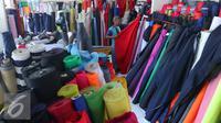 Pekerja merapikan gulungan kain di Pasar Cipadu, Tangerang, Selasa (30/8).Dirjen Industri Kimia, Tekstil, dan Aneka (IKTA) Kemenperin optimistis kinerja industri tekstil dan produk tekstil nasional akan gemilang. (Liputan6.com/Angga Yuniar)