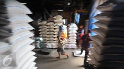 Pekerja memanggul karung Beras di pasar induk Cipinang, Jakarta, Selasa (27/12). Kecukupan kebutuhan tersebut diharapkan bisa menahan laju kenaikan harga barang pokok. (Liputan6.com/Angga Yuniar)