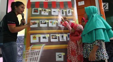 Karyawan mengajar mengelola keuangan melalui Kedai DBS kepada anak-anak di yayasan Rumpun Anak Pesisir di Jakarta Utara, Selasa (17/7). Anak-anak diajarkan bagaimana mengelola keuangan secara sederhana. (Liputan6.com/Angga Yuniar)
