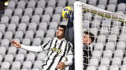 Pemain Juventus Alvaro Morata (kiri) berebut bola dengan kiper Genoa Alberto Paleari (kanan) pada pertandingan babak 16 besar Coppa Italia di Allianz Stadium, Turin, Italia, Rabu (13/1/2021). Juventus melaju ke perempat final usai menaklukkan Genoa 3-2. (Marco Alpozzi/LaPresse via AP)