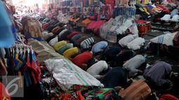 Sejumlah umat muslim saat melakukan shalat Jumat di tengah-tengah barang jualannya, Tanah Abang , Jakarta, Jumat (26/6/2015). Hal ini dilakukan untuk menghindari incaran tangan-tangan jahil . (Liputan6.com/Johan Tallo)
