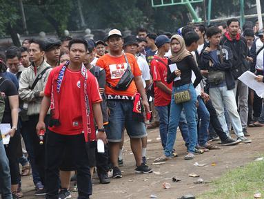 Suporter tim Persija mengantre menukarkan voucher on-line dengan tiket masuk Stadion GBK di Lapangan Blok S, Jakarta, Minggu (9/12). Mereka akan menyaksikan laga penentuan gelar juara Persija di Liga 1 Indonesia 2018. (Liputan6.com/Helmi Fithriansyah)