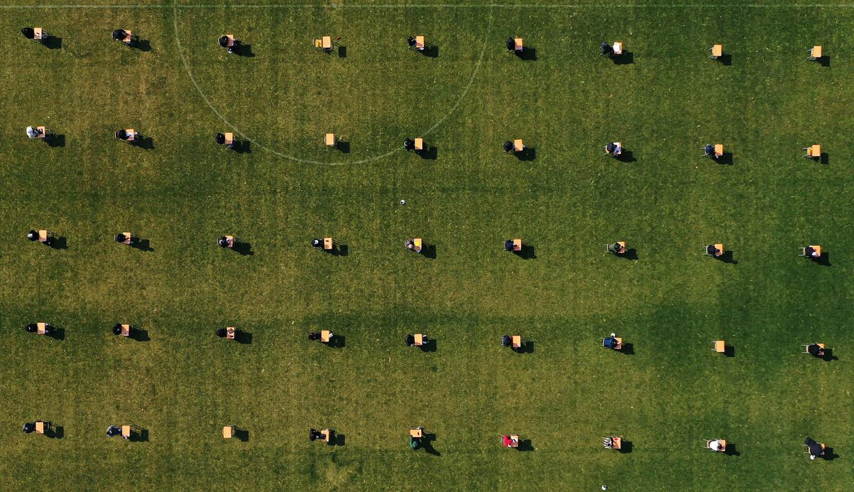 Pelamar kerja saat mengikuti ujian tertulis selama tes rekrutmen untuk Ansan Urban Corporation di stadion Wa di Ansan, Korea Selatan (4/8/2020).  Perekrutan yang dilakukan di tengah pandemi COVID-19 mengikuti aturan jarak sosial, di mana peserta jarak 5 meter per orang. (AP Photo/Hong Ki-won)