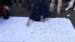 Warga menandatangani spanduk dukungan anti hoax di kawasan Bundaran Hotel Indonesia, Jakarta, Minggu (18/11). PB HMI mensosialisasikan Hoax sebagai ancaman demokrasi di Indonesia. (Liputan6.com/Helmi Fithriansyah)