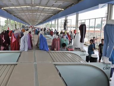 Pengunjung melintasi sejumlah kios pedagang di Skybridge atau jembatan multiguna Tanah Abang, Jakarta, Selasa (11/12). Ini merupakan hari keempat uji coba Skybridge Tanah Abang. (Merdeka.com/Iqbal Nugroho)