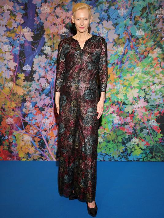 Tilda Switon tampil mengenakan jumpsuit renda berwarna-warni dari koleksi Chanel Haute Couture SS 2021, sepatu, dan makeup oleh Chanel. Tampilan ini diambil dari look 23. Foto: Document/Chanel.