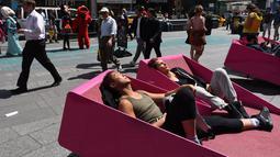 Sejumlah orang menerima tantangan untuk berjemur di sebuah tempat yang telah disediakan di Times Square, New York, AS, Selasa (2/5). (AFP PHOTO / TIMOTHY A. CLARY)