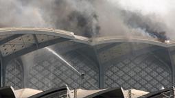 Pasukan Pertahanan Sipil Arab Saudi memadamkan kebakaran yang melanda Stasiun Kereta Api Cepat Haramain di kota Jeddah, Minggu (29/9/2019). Kebakaran terjadi pada pukul 12.35 waktu setempat di atap lantai empat gedung stasiun. (Photo by - / AFP)