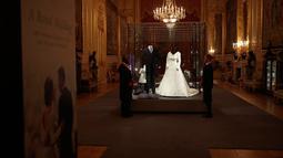 Petugas berjaga dekat gaun pernikahan Putri Eugenie dan sang suami, Jack Brooksbank selama pratinjau media di Kastil Windsor, London, Kamis (28/2). Gaun itu akan dipajang sebagai bagian dari pameran yang berlangsung hingga 22 April 2019. (AP/Matt Dunham)