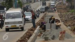 Pekerja saat menyelesaikan proyek rehabilitasi ruas jalan Ciputat-Pamulang, Tangerang Selatan, (28/1). Akibat pengerjaan lalu lintas mengalami kemacetan. (Liputan6.com/Faisal R Syam)