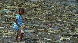 Seorang anak perempuan berjalan di tumpukan sampah di permukiman kumuh di sepanjang garis pantai Pantai Baseco di Manila (28/9/2019). Pada 12 Februari 2002, Presiden Gloria Macapagal Arroyo menyatakan Baseco sebagai tempat tinggal.  (AFP Photo/Maria Tan)