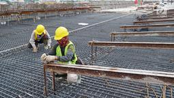 Pekerja menyelesaikan konstruksi proyek pembangunan Jalan Tol Medan - Binjai seksi I di Deli Serdang, Sumatera Utara, Rabu (6/3). Jalan Tol Medan - Binjai sepanjang 17 km terbagi atas tiga seksi. (Liputan6.com/HO/Eko)