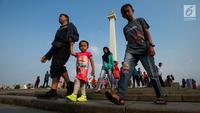 Sejumlah pengunjung berjalan-jalan di kawasan Monumen Nasional (Monas) Jakarta, Kamis (6/6/2019). Monas yang merupakan Ikon Ibu Kota itu menjadi salah satu tujuan wisata untuk mengisi libur Lebaran. (merdeka.com/Imam Buhori)
