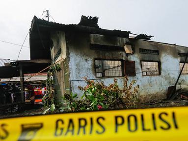 Garis polisi terpasang di sekitar lokasi kebakaran pabrik korek gas di Binjai, Langkat, Sumatera Utara, (21/6/2019). Sebanyak 30 orang tewas dalam kejadian tersebut. (KUMBARA/AFP)