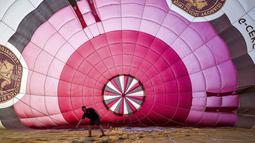 Seorang pilot memeriksa balon udara selama festival tahunan balon udara panas Bristol di Bristol, Inggris (8/8/2019). Festival balon udara ini diadakan selama empat hari dari 8-11 Agustus 2019. (Ben Birchall/PA via AP)