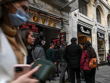 Orang-orang mengantre di luar agen penukaran mata uang dekat alun-alun Taksim ketika lira Turki terperosok ke level terendah sepanjang sejarah di Istanbul, Senin (25/10/2021). Lira melemah imbas pengusiran duta besar AS dan sembilan negara Barat lainnya oleh Presiden Tayyip Erdogan. (Ozan KOSE/AFP)