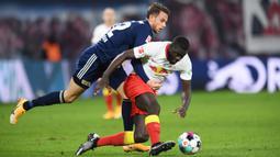 Bek RB Leipzig, Dayot Upamecano, berebut bola dengan penyerang Union Berlin, Marcus Ingvartsen, pada laga lanjutan Liga Jerman di Red Bull Arena Stadium, Kamis (21/1/2020) dini hari WIB. RB Leipzig menang tipis 1-0 atas Union Berlin. (AFP/Annegret Hilse/pool)