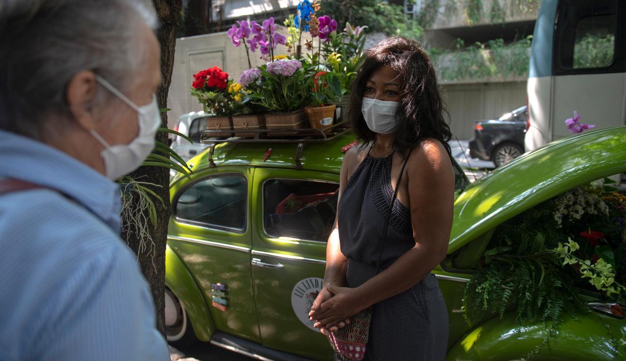 Roberta Machado (kanan) asal Brasil dan pelanggan berbincang di sebelah VW Beetle 1969 miliknya yang diubah menjadi toko bunga keliling di Copacabana, Rio de Janeiro, Rabu (14/10/2020). Perempuan 51 tahun ini mengubah VW kodok untuk bertahan dari krisis akibat pandemi COVID-19. (MAURO PIMENTEL/AFP)