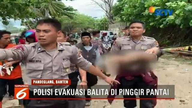 Petugas gabungan evakuasi bocah laki-laki korban tsunami Anyer di pinggir Pantai Karang Bolong. Saat ditemukan, bocah tersebut dalam keadaan tanpa busana dan tampak lemas.