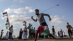 Pria Palestina memakai ketapel untuk melemparkan batu ke arah pasukan Israel saat bentrok di Khan Yunis, Jalur Gaza, Jumat (13/9/2019). Warga menyerukan pencabutan blokade Israel di Jalur Gaza. (SAID KHATIB/AFP)