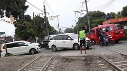Kendaraan menyeberangi perlintasan kereta api di Lenteng Agung, Jakarta, Selasa (13/3). Untuk mengurai kemacetan imbas antrian kendaraan berputar balik di pintu kereta IISIP, Pemprov DKI berencana membangun flyover U-Turn. (Liputan6.com/Immanuel Antonius)