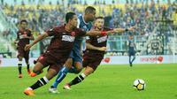 Penyerang Arema, Thiago Furtuoso, dikawal dua pemain PSM pada laga di Stadion Kanjuruhan, Malang, Minggu (13/5/2018). (Bola.com/Iwan Setiawan)