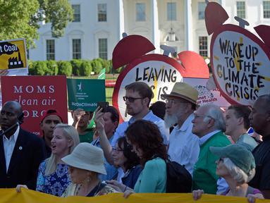Demonstran berkumpul di dekat Gedung Putih di Washington, AS, Kamis (1/6). Demonstran memprotes keputusan Donald Trump yang menarik AS dari perjanjian Paris tentang perubahan iklim yang disepakati pada 2015. (AP/ Susan Walsh)
