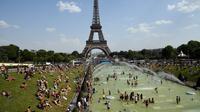 Turis dan warga menyejukkan diri dan berjemur di kolam Trocadero Fountains (air mancur Trocadero) dekat Menara Eiffel di Paris, Kamis (25/7/2019). Gelombang panas di Eropa mencapai puncaknya, bahkan suhu di ibu kota Prancis mencapai di atas 41 derajat Celcius. (Bertrand GUAY / AFP)