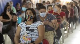 "Sejumlah wanita duduk setelah menerima sumbangan pembalut dan perlengkapan kebersihan perempuan lainnya di tengah pandemi COVID-19 di favela Paraisopolis, di Sao Paulo, Brasil (24/5/2021). Sumbangan ini disediakan oleh LSM lokal ""G10 Favelas"". (AP Photo/Andre Penner)"