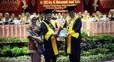 Mantan Wakil Presiden Jusuf Kalla (kiri) didampingi sang istri, Mufidah Kalla berjabat tangan dengan Rektor Universitas Negeri Padang (UNP) Ganefri (kanan) saat penganugerahan gelar doktor kehormatan (Dr. Honoris Causa), di kampus tersebut di Padang, Kamis (5/12/2019). (FOTO: Tim Media JK)