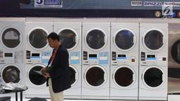 Penjaga stan melintas di depan mesin cuci di pameran Expo Clean dan Expo Laundry 2018, Jakarta, Selasa (27/3). Pameran tersebut merupakan pameran dagang yang menampilkan produk dan jasa dalam industri cleaning dan laundry. (Liputan6.com/Angga Yuniar)