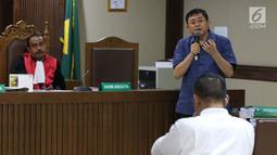 Terdakwa dugaan menghalangi proses penyidikan KPK, Lucas (baju biru) memberi pertanyaan kepada salah satu saksi ahli pada sidang lanjutan di Pengadilan Tipikor, Jakarta, Kamis (21/2). Sidang mendengar dua saksi ahli. (Liputan6.com/Helmi Fithriansyah)